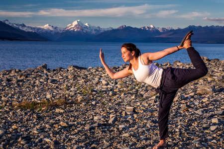 Girl do yoga at Pukaki glacier lake with turquoise blue water and mountains landscape. Pukaki lake at Aoraki - Mount Cook National Park, New Zealand. Mount Cook, New Zealand - December 23 2017. Editorial