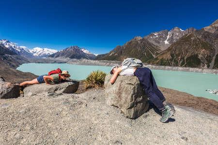 Female tourists resting on the rocks on the stomach at glacier lake. Tasman glacier, Aoraki - Mount Cook National Park, New Zealand. Mount Cook, New Zealand - December 24 2017.
