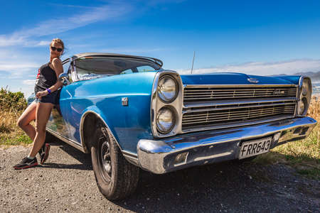 Girl posing near classic car with amazing ocean view at the background. Punakaiki, New Zealand - January 01 2018.