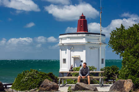 Man sits on a bench near lighthouse at Bluff, New Zealand. Bluff, New Zealand - December 19 2017.