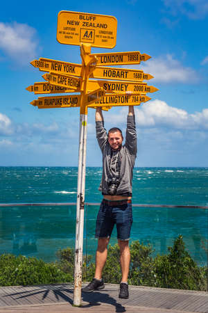 Man hangs from the world's southernmost signpost in Bluff, South Island. Global signpost shows world distances measured from Bluff, tourist destination. Bluff, New Zealand - December 19 2017.