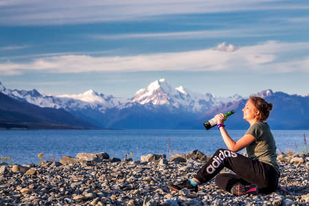 Girl drinks wine while enjoying view of Pukaki glacier lake with blue water and mountains. Pukaki lake at Aoraki - Mount Cook National Park, New Zealand. Mount Cook, New Zealand - December 23 2017.