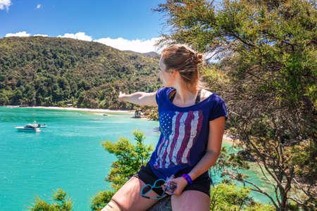 Girls resting on the rock after hiking a trail. Abel Tasman National Park, New Zealand - December 28 2017.