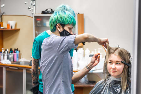 A couple of hairdressers with colored hair and bright tattoos paint the head of an attractive girl in purple. Minsk, Belarus - April 14 2020.