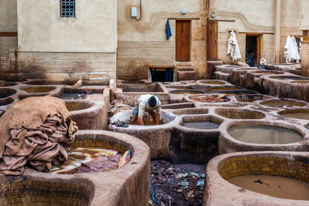 Men working in traditional leather dyeing in a traditional tanneries, Medina of Fez, Morocco. Fes, Morocco. April 10 2016. Foto de archivo - 156208612