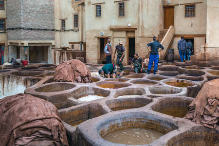 Men working in traditional leather dyeing in a traditional tanneries, Medina of Fez, Morocco. Fes, Morocco. April 10 2016. Editorial