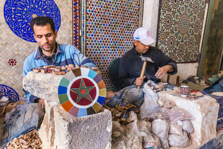 Local artisan make mosaic pieces and creating handmade items in old Medina market. Fes, Morocco - April 10 2016. Foto de archivo - 156208608