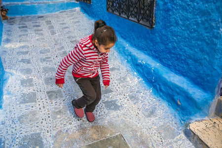 Girl plays outside at the famous blue city of Chefchaouen, Morocco. Chefchaouen, Morocco - April 11 2016. Foto de archivo - 156208609