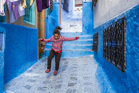 Girl plays outside at the famous blue city of Chefchaouen, Morocco. Chefchaouen, Morocco - April 11 2016. Foto de archivo - 156208610