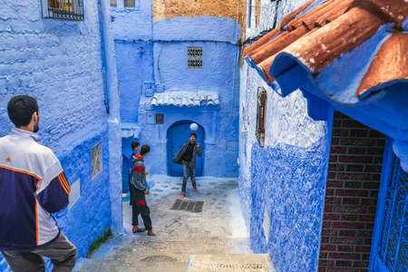 Boys play outside at the famous blue city of Chefchaouen, Morocco. Chefchaouen, Morocco - April 11 2016.