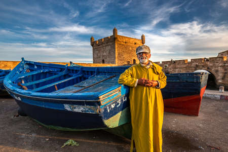 Elderly fisherman wearing traditional kaftan near blue boat at the harbor in Essaouira, Morocco. Essaouira, Morocco - April 14 2016. Редакционное