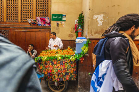 Seller at the stand with oranges in the market of Fes, Morocco. Fes, Morocco. April 10 2016.