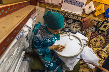 Local woman sew with traditional frame and creating handmade textile in old Medina market. Fes, Morocco - April 10 2016. Редакционное