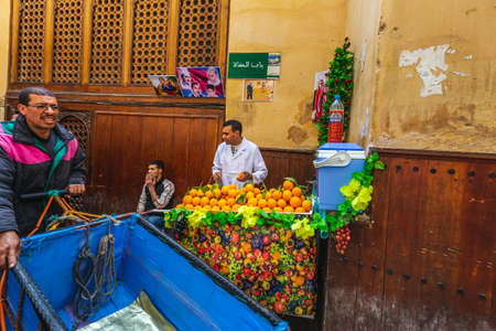 Seller at the stand with oranges in the market of Fes, Morocco. Fes, Morocco. April 10 2016. Foto de archivo - 156207680