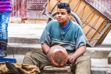 Local artisan pounding on copper pot and creating handmade dishes in old Medina market. Fes, Morocco - April 10 2016.