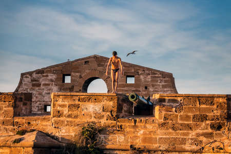 Boy jumping into the water from old city walls in Essaouira, Morocco. Shot at sunset. Essaouira, Morocco - April 14 2016. Foto de archivo - 156207674