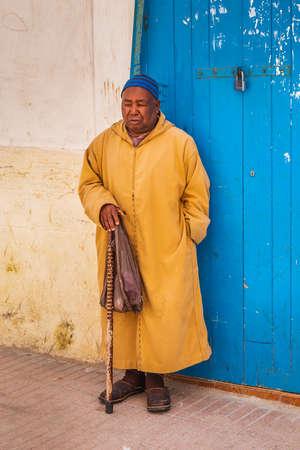 Man wearing traditional kaftan at the streets of Essaouira, Morocco. Essaouira, Morocco - April 14 2016.