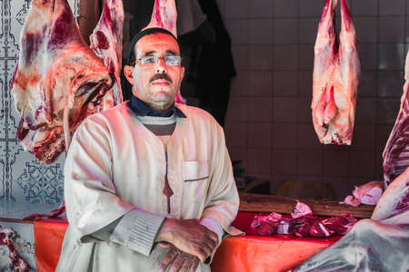 Butcher portrait near meat hanging outside a butchers shop without refrigiration in Essaouira, Morocco. Essaouira, Morocco - April 14 2016. Редакционное