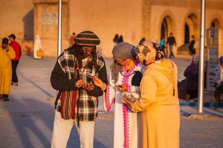 Man sells souvenirs to tourists in Essaouira, Morocco. Shot at sunset. Essaouira, Morocco - April 14 2016. Foto de archivo - 156132621