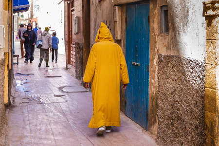 Man wearing traditional kaftan at the streets of Essaouira, Morocco. Essaouira, Morocco - April 14 2016. Foto de archivo - 156207662