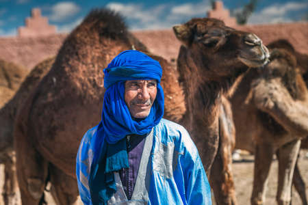 Berber and his camel dressed in traditional clothes and turban. Owner of camels at the camel market in Guelmim. Guelmim, Morocco - April 16 2016.