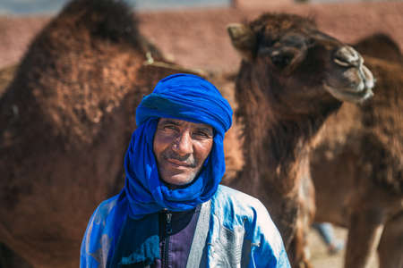Local berber dressed in traditional clothes and turban. Owner of camels at the camel market in Guelmim. Guelmim, Morocco - April 16 2016.