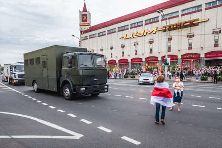 Women with child block road for police vehicles during peaceful protests in Belarus against rigged presidential elections in Minsk, Belarus. Minsk, Belarus - August 30 2020. Foto de archivo - 154376238