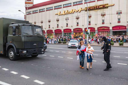 Women with child block road for police vehicles during peaceful protests in Belarus against rigged presidential elections in Minsk, Belarus. Minsk, Belarus - August 30 2020.
