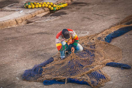 Fisherman fixes the net at the harbor in Essaouira, Morocco. Imagens
