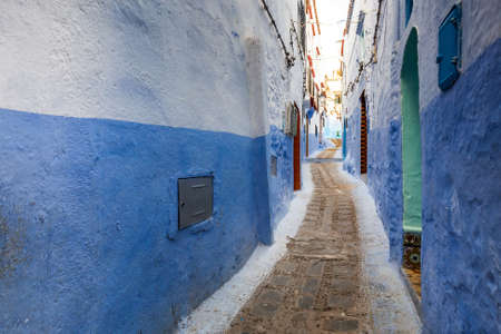 Typical moroccan narrow street in Chefchaouen. Blue city medina in Morocco with blue painted walls. Foto de archivo - 156106348