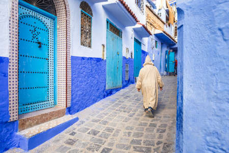 Typical moroccan narrow street in Chefchaouen. Blue city medina in Morocco with blue painted walls. Foto de archivo - 156106355