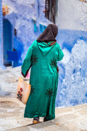 Woman wearing traditional clothes walks in the famous blue city of Chefchaouen, Morocco. Foto de archivo