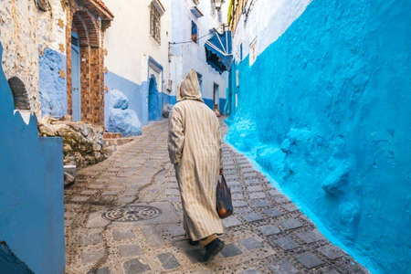 Typical moroccan narrow street in Chefchaouen. Blue city medina in Morocco with blue painted walls. Foto de archivo - 156106777