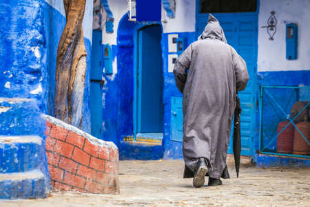 Man wearing traditional clothes walks in the famous blue city of Chefchaouen, Morocco.