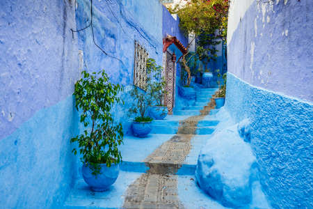 Typical moroccan narrow street in Chefchaouen. Blue city medina in Morocco with blue painted walls. Foto de archivo - 156105813