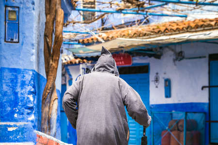 Man wearing traditional clothes walks in the famous blue city of Chefchaouen, Morocco. Foto de archivo - 156105821