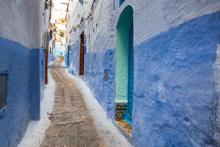 Typical moroccan narrow street in Chefchaouen. Blue city medina in Morocco with blue painted walls. Foto de archivo - 156105833