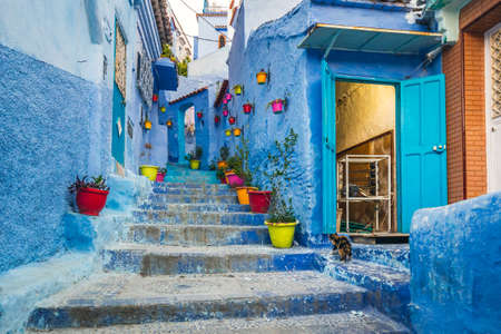 Typical moroccan narrow street in Chefchaouen. Blue city medina in Morocco with blue painted walls. Foto de archivo - 156105909