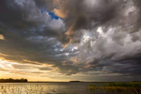 Amazing sunset at the Braslaw lakes with the cloudy sky. Braslaw district, Belarus. 免版税图像