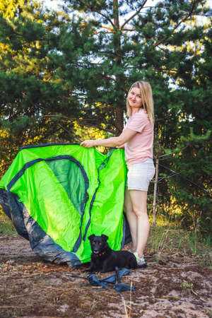 Beautiful girl and a dog pitching tent. Camping and outdoor concept. 免版税图像