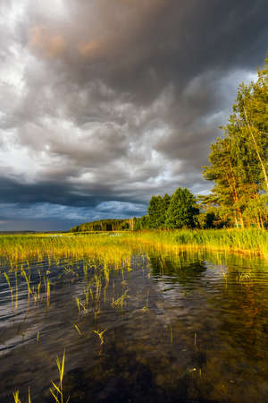 Amazing sunset at the Braslaw lakes with the cloudy sky. Braslaw district, Belarus. Foto de archivo