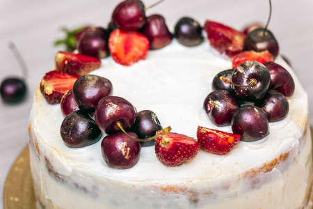 Cherries and strawberries with edible gold on top of cheesecake with coconut.