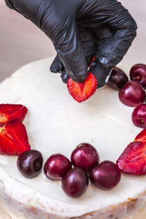 Female hand in black glove puts cherries and strawberries on top of cheesecake with coconut. Stok Fotoğraf