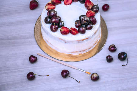 Cherries and strawberries with edible gold on top of cheesecake with coconut. Blue toning. Stok Fotoğraf