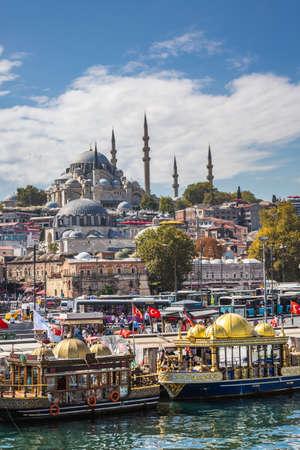 Suleymaniye Mosque shot from Galata Bridge with colorful boats in Istanbul, Turkey. Istanbul, Turkey - September 30 2020.