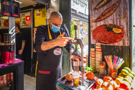 Local Turkish man makes a fresh pomegranate juice at his fruit stall. Pomegranate juice is a famous local beverage in Turkey. Istanbul, Turkey - September 30 2020. Publikacyjne