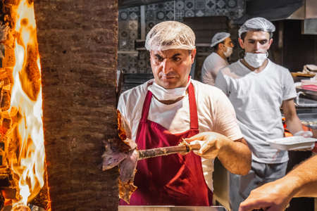 Cook Cutting Meat From a Doner Kebab in in Uskudar, Istanbul, Turkey. Istanbul, Turkey - October 01 2020. Publikacyjne