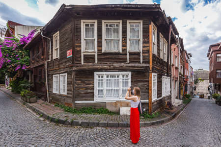 Woman in the red dress on the old streets of Istanbul taking photos. Istanbul, Turkey - September 30 2020.