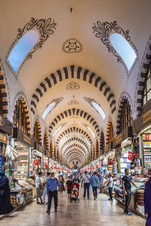 People shopping in the Grand Bazar, handmade pillows, bags and carpets are on the wall for sale. Souvenirs in famous Grand Bazaar. Istanbul, Turkey - September 30 2020.
