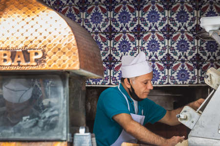 In Turkey the locals prefer hand-made bread, each family buying at least 5 breads each day. Image of a baker in a traditional Turkish bakery. Istanbul, Turkey - September 30 2020.